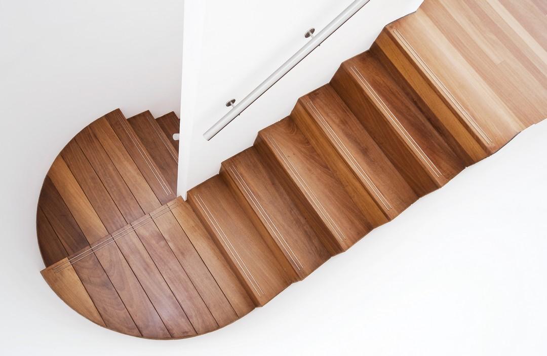 Escaliers en bois dans un intérieur blanc immaculé.