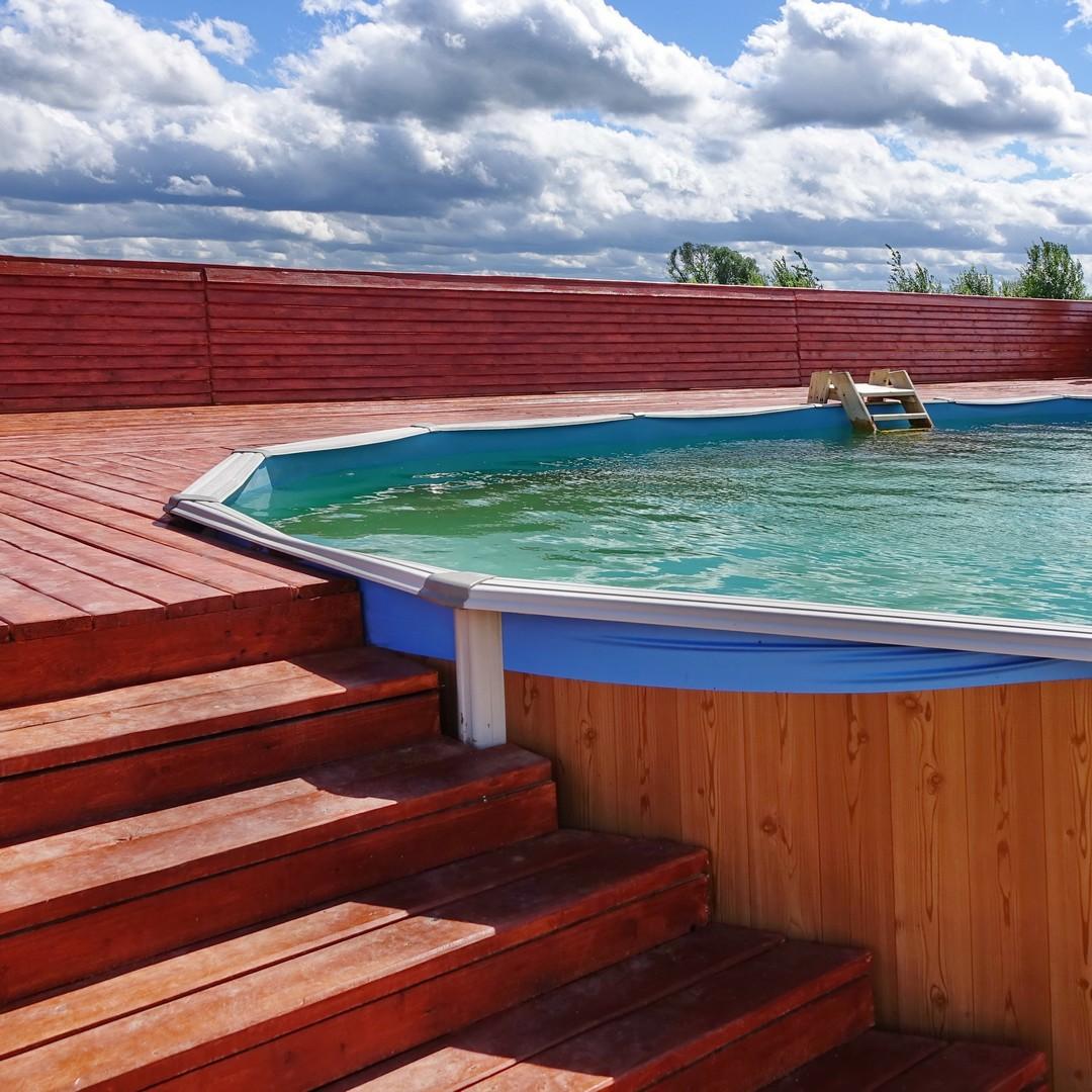 Escalier en bois qui donne sur une piscine.