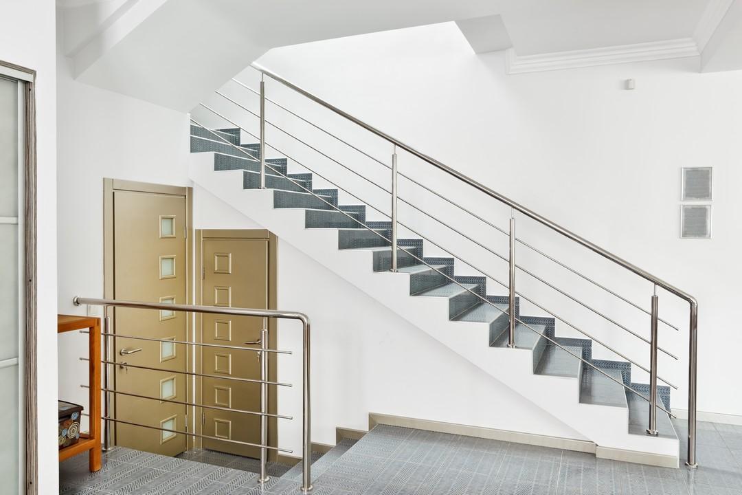 Un escalier en carrelage, la rampe en métal dans un bureau.