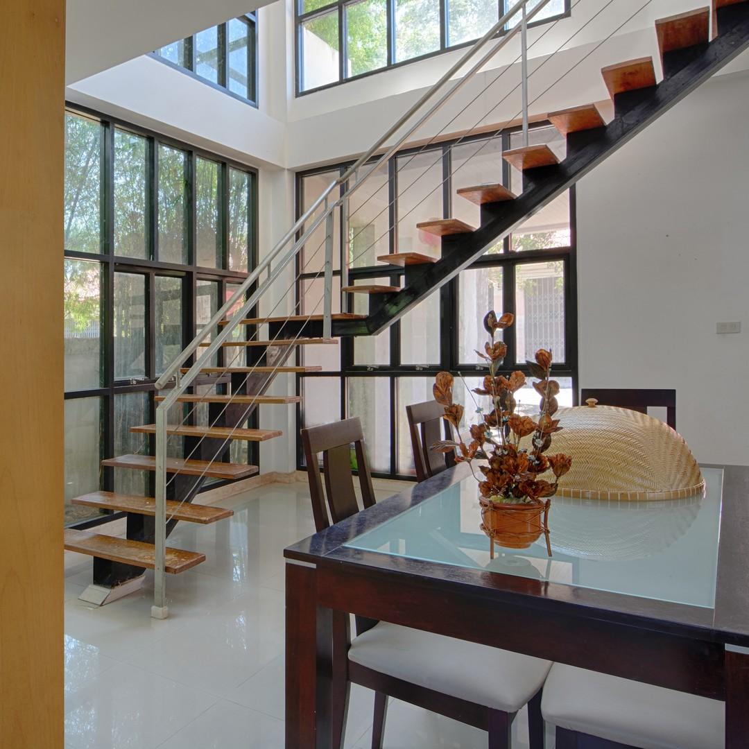 Intérieur avec un escalier suspendu au milieu de la pièce.